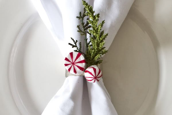 Glue some mints to a pretty ribbon and tie around a napkin adding some real greenery!